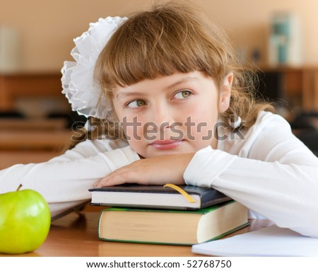 Schoolgirl's portrait at school desk with her books