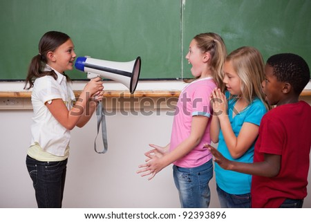 Schoolgirl screaming through a megaphone to her classmates in a classroom - stock photo