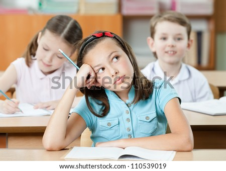 Schoolgirl sits at the desk and dreams - stock photo