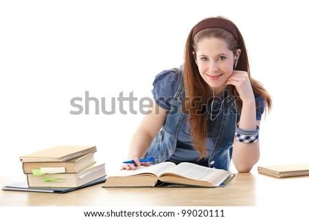 Schoolgirl sitting at table at home, learning, smiling. - stock photo