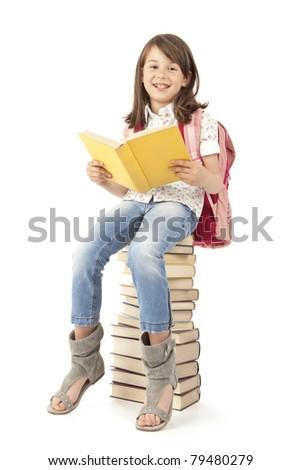 Schoolgirl sitting on the books - stock photo