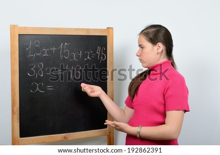 Schoolgirl solves a mathematical equation on a blackboard - stock photo