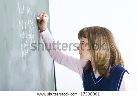 Schoolgirl standing and writing something on chalkboard. Side view. - stock photo