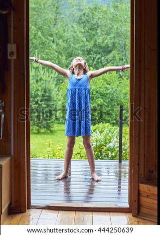 Schoolgirl  standing bare feet on the porch enjoying warm summer rain