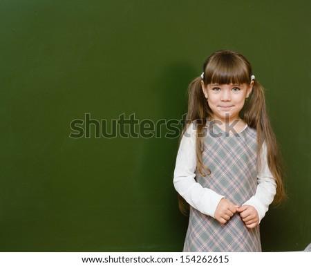 Schoolgirl standing in class near a green blackboard. looking at camera. - stock photo