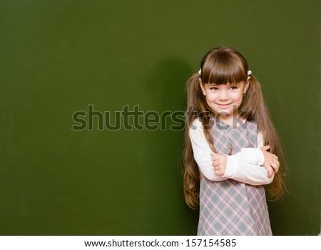 Schoolgirl standing in class near a green blackboard. looking away - stock photo