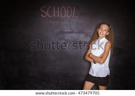 Schoolgirl stands near a black slate. Free space. Black background. School concept