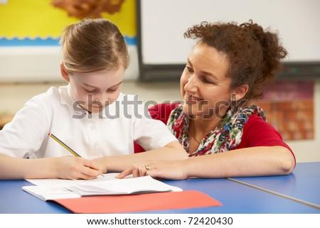 Schoolgirl Studying In Classroom With Teacher - stock photo