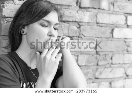 Schoolgirl teenager smokes outdoor on brick wall background. Smoking is harmful to our health. Black and white edition - stock photo