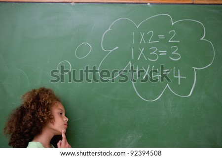 Schoolgirl thinking about algebra in front of a blackboard - stock photo