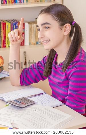 schoolgirl thinking and doing homework - stock photo