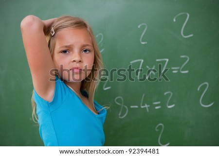 Schoolgirl thinking while scratching the back of her head in front of a blackboard - stock photo