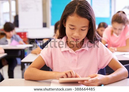 Schoolgirl using tablet computer in elementary school class
