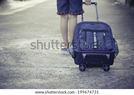 schoolgirl walk alone to school with school bag - stock photo