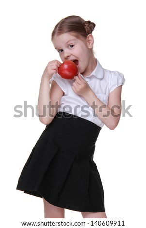 Schoolgirl wearing white blouse and black skirt and holding red apple on Education theme/Portrait of beautiful little schoolgirl with fresh organic red apple - stock photo