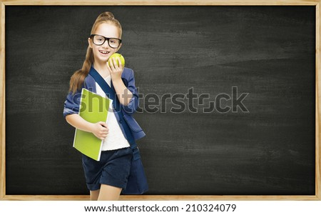 Schoolgirl with book apple and blackboard, school girl child on black board background, elementary education concept - stock photo