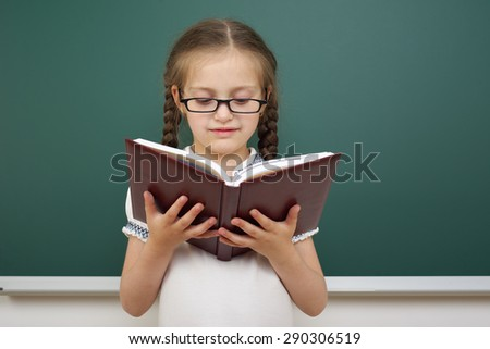 Schoolgirl with book near the school board - stock photo