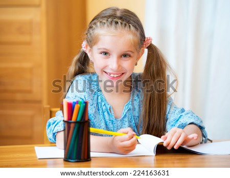 Schoolgirl with colored felt-tip pens in the classroom - stock photo