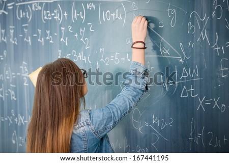 Schoolgirl with glasses solving math problem on blackboard - stock photo