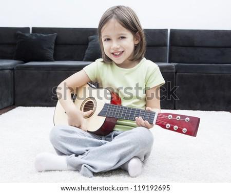 schoolgirl with guitar sitting on the floor - stock photo
