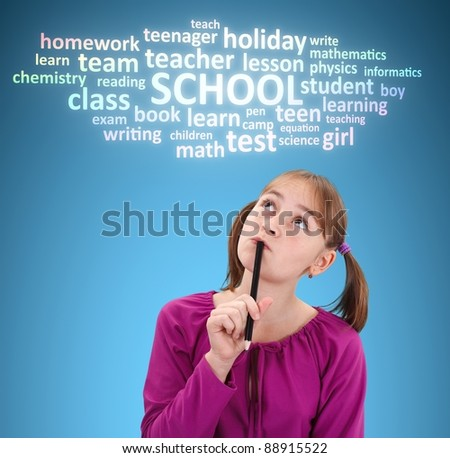 Schoolgirl with pen, thinking about school. Tag cloud over her head - stock photo