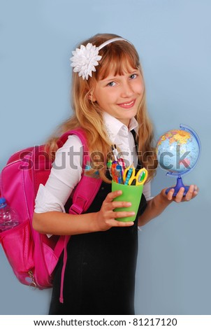schoolgirl with pink backpack with globe and school supplies in hands against blue background - stock photo