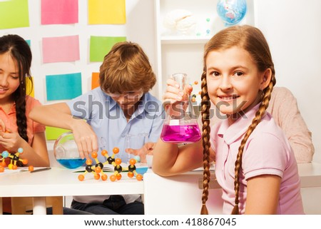Schoolgirl with plaits holding flask at school lab - stock photo