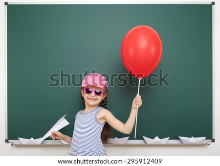 Schoolgirl with red balloon near the school board - stock photo