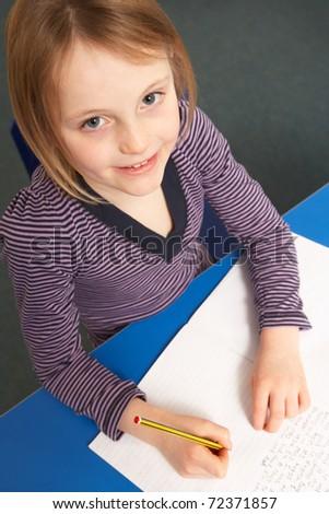 Schoolgirl Working In Classroom - stock photo