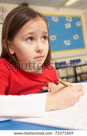 Schoolgirl Working In Classroom Under Pressure - stock photo