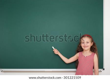 Schoolgirl write on the school board - stock photo