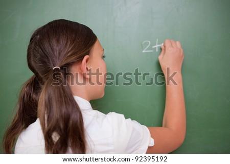Schoolgirl writing an addition on a blackboard - stock photo