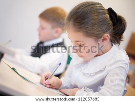 Schoolgirl writing her task with  boy sitting near by