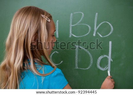 Schoolgirl writing letters on a blackboard - stock photo