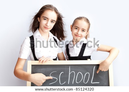 schoolgirls about a school board with a word school the written chalk