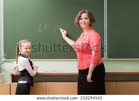 Schoolgirls and teacher in the classroom - stock photo