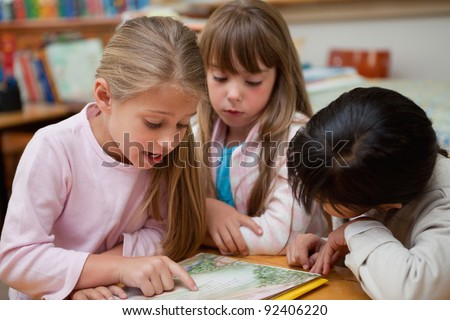 Schoolgirls reading a fairy tale together in a classroom