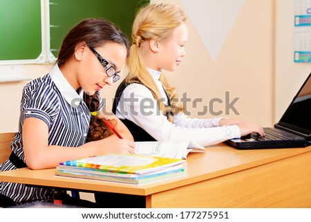 Schoolgirls sit at their desk during a lesson. Education. - stock photo