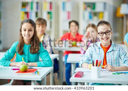 Schoolgirls sitting by desks at lesson