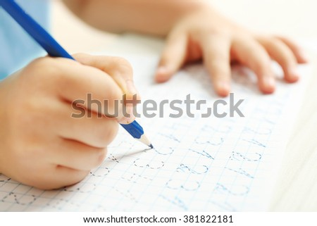 Schoolkid learns to write on sheet of paper, closeup