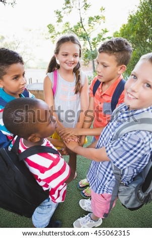 Schoolkids putting their hands together in campus at school - stock photo