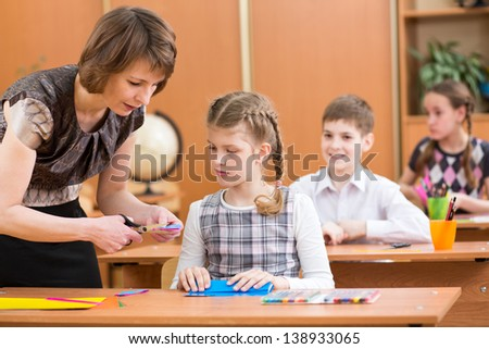Schoolkids work at labour lesson. Teacher helping to pupil. - stock photo