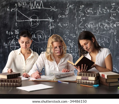 schoolmate studying and reading books against a blackboard