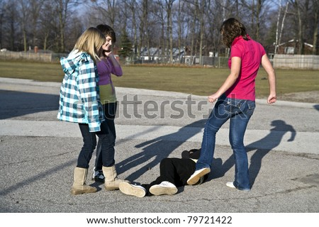 Schoolyard bullies, later afternoon signified by the long shadows, concept of this taking place after school - stock photo