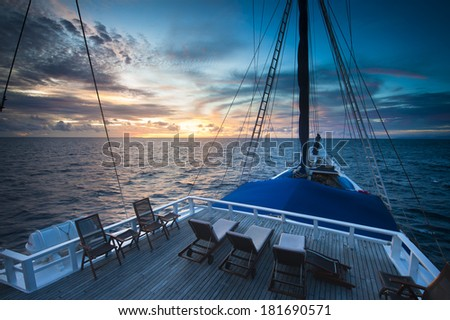 Schooner Sailing in Indonesia. A traditional Indonesian Phinisi sailboat cruises the Spice Islands passing remote areas in the Banda Sea. - stock photo