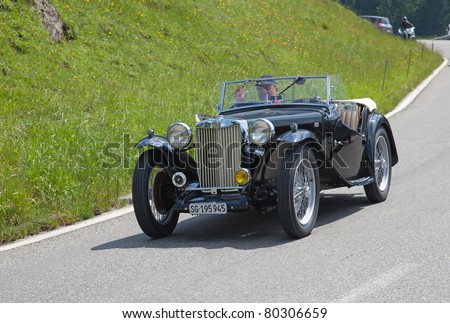 """SCHWAEGALP - JUNE 27: Morgan MG Plus Four car leaving the 7th International """"Oldtimer meeting"""" in Schwaegalp, Switzerland on June 27, 2010.Around 4'5000 """"Morgan +4"""" was produced between 1950 and 1961. - stock photo"""