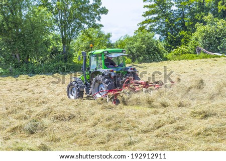 SCHWALBACH, GERMANY - JUNE 16, 2013:  tractor in meadow making hay in Schwalbach, Germany. Hay is grass, legumes or other plants that have been cut, dried, and stored for use as animal fodder.