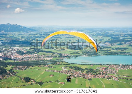 SCHWANGAU, GERMANY - AUGUST 23: Unknown paraglider on mount Tegelberg in Schwangau, Germany on August 23, 2015. Tegelberg is one of the most popular paragliding areas in Germany.  - stock photo