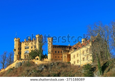 SCHWANGAU, GERMANY - DECEMBER 2015 : The facade of Hohenschwangau Castle on the hill in Schwangau, Germany on December 26, 2015. It is the neo-gothic styled where King Ludwig II. spent his childhood - stock photo