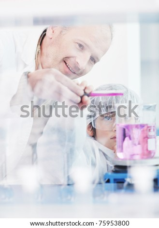 science and chemistry classes with teacher and young school boy at bright lab - stock photo
